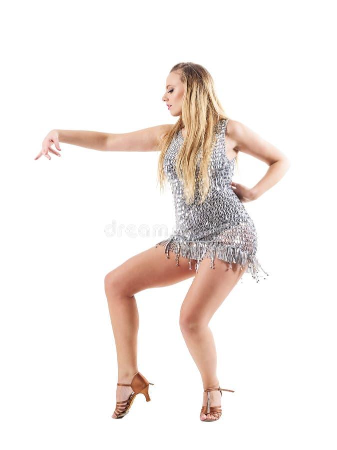 Στάση χορογραφίας χορού της ξανθής γυναίκας στο λαμπρό μεταλλικό ασημένιο φόρεμα Πλάγια όψη στοκ εικόνες