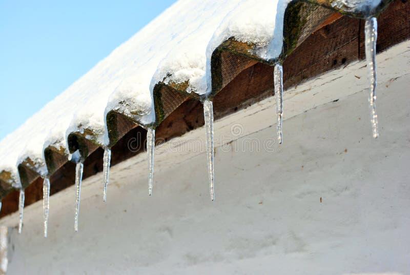 Στέγες πλακών με τα παγάκια που καλύπτονται το χιόνι, που καλύπτονται με με το χιόνι, το άσπρο υπόβαθρο τοίχων στοκ εικόνα