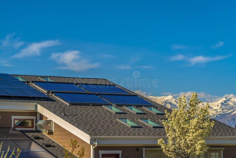 Στέγη ενός σπιτιού με τα ηλιακά πλαίσια και τους φεγγίτες που αντιμετωπίζονται μια ηλιόλουστη ημέρα στοκ φωτογραφία με δικαίωμα ελεύθερης χρήσης