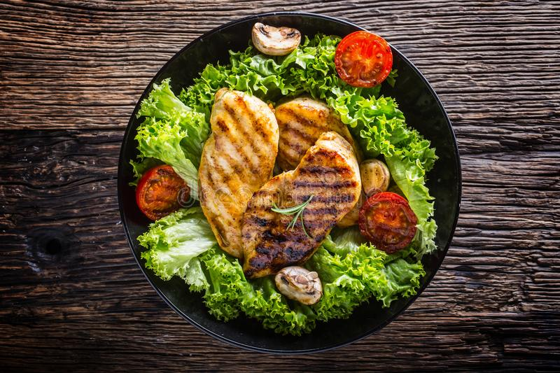 Στήθος κοτόπουλου σχαρών που ψήνεται και σχαρών στήθος κοτόπουλου με τις ντομάτες και τα μανιτάρια σαλάτας μαρουλιού στοκ φωτογραφίες