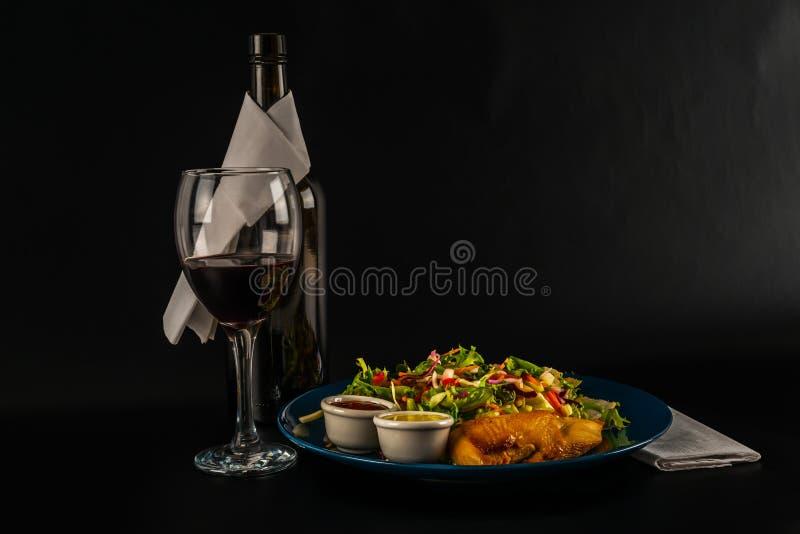 Στήθος κοτόπουλου ψητού με μίγμα μαρουλιού και δύο σάλτσες, μπλε πιάτο στοκ εικόνα