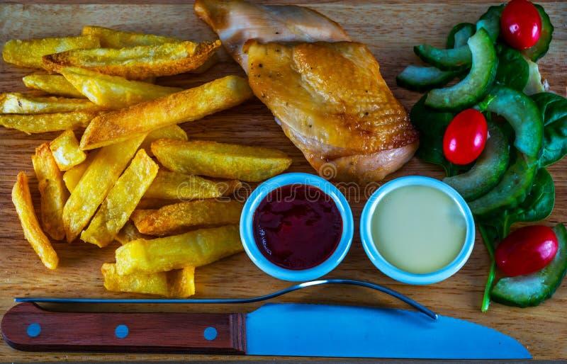 Στήθος κοτόπουλου ψητού με τα τσιπ, σαλάτα με τις ντομάτες και cucumbe στοκ εικόνα με δικαίωμα ελεύθερης χρήσης
