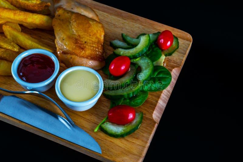 Στήθος κοτόπουλου ψητού με τα τσιπ, σαλάτα με τις ντομάτες και cucumbe στοκ εικόνες