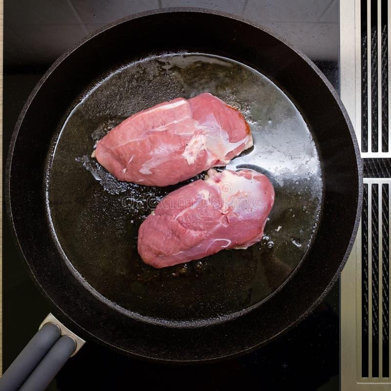 Στήθος παπιών στο τηγάνι με το στάλαγμα σε μια σόμπα στοκ εικόνες