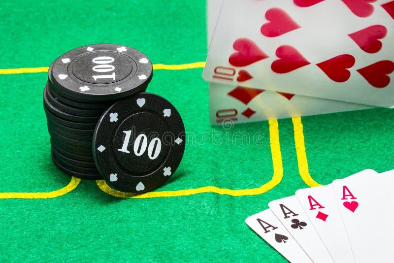 Στήλη των μαύρων τσιπ για τις μειωμένες κάρτες πόκερ και ένας συνδυασμός τεσσάρων άσσων στοκ εικόνες με δικαίωμα ελεύθερης χρήσης