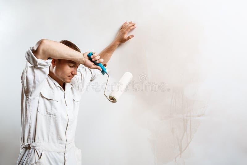 Στήριξη εργαζομένων, που κρατά τον κύλινδρο πέρα από τον άσπρο τοίχο διάστημα αντιγράφων στοκ εικόνες με δικαίωμα ελεύθερης χρήσης
