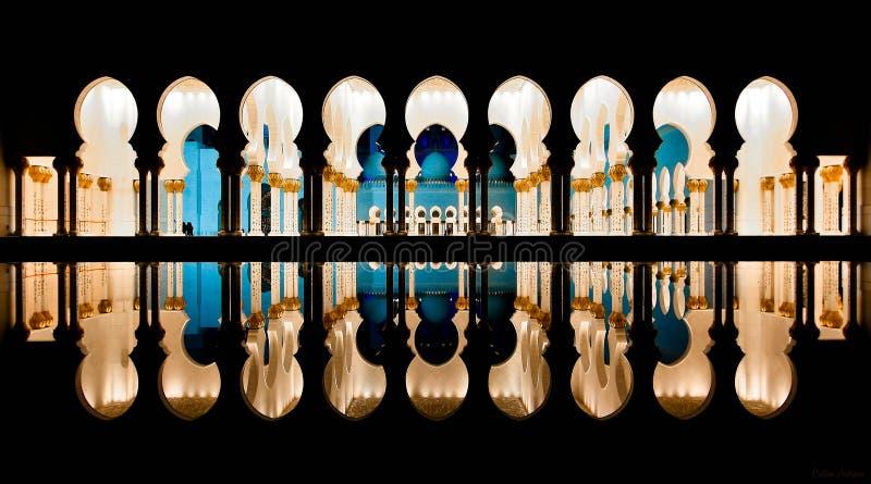 Στήλες μουσουλμανικών τεμενών που απεικονίζουν στο νερό τη νύχτα στοκ εικόνα