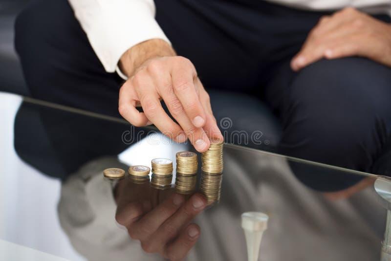 Στήλη χρημάτων οικοδόμησης χεριών επιχειρηματιών στοκ εικόνες