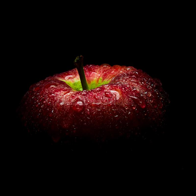 Σταγονίδιο νερού στη στιλπνή επιφάνεια του κόκκινου μήλου στο μαύρο υπόβαθρο στοκ εικόνες