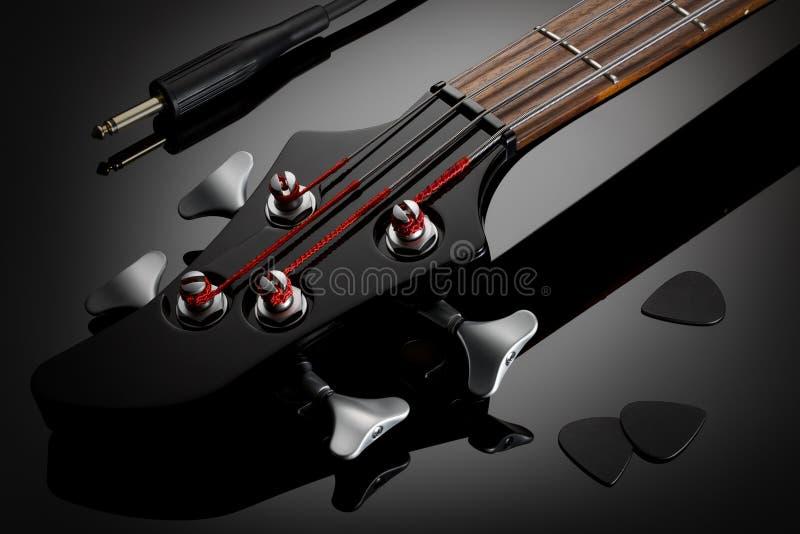 Σταθερό μέρος τόρνου της ηλεκτρικής βαθιάς κιθάρας, του ακουστικών καλωδίου και των επιλογών στοκ εικόνα