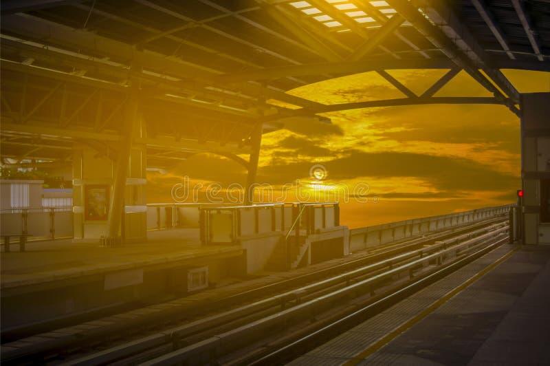 Σταθμός τρένου ουρανού στο ηλιοβασίλεμα με τον όμορφο κίτρινο ουρανό στοκ φωτογραφία