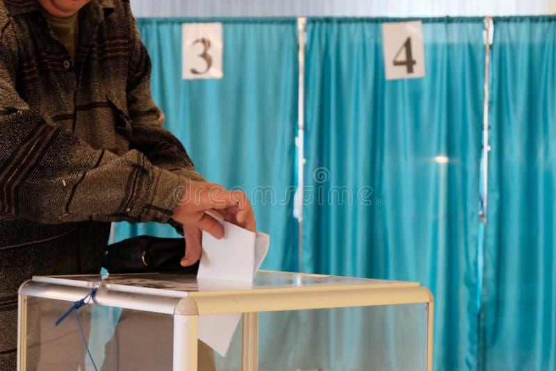 Σταθμός ψηφοφορίας Σε εθνικό επίπεδο ψηφοφορία, εκλογές Ένα άτομο βάζει ένα φύλλο εγγράφου σε ένα διαφανές κιβώτιο r Καμπίνες με  στοκ εικόνα