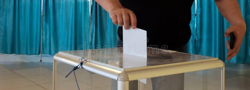 Σταθμός ψηφοφορίας Σε εθνικό επίπεδο ψηφοφορία, εκλογές Ένα άτομο βάζει ένα φύλλο εγγράφου σε ένα διαφανές κιβώτιο r   στοκ εικόνα