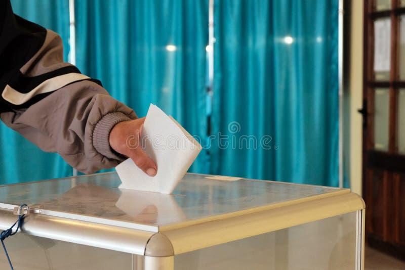Σταθμός ψηφοφορίας E Το αρσενικό χέρι βάζει ένα ψηφοδέλτιο σε ένα διαφανές κιβώτιο r   Σε εθνικό επίπεδο ψηφοφορία, στοκ φωτογραφία