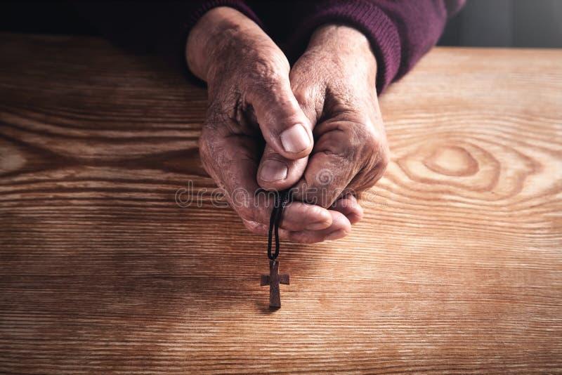 Σταυρός στα χέρια της ηλικιωμένης γυναίκας στοκ εικόνες