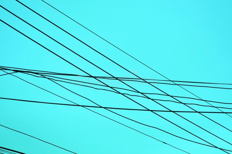 Σταυρώνοντας ηλεκτροφόρα καλώδια στο μπλε υπόβαθρο στοκ φωτογραφίες με δικαίωμα ελεύθερης χρήσης