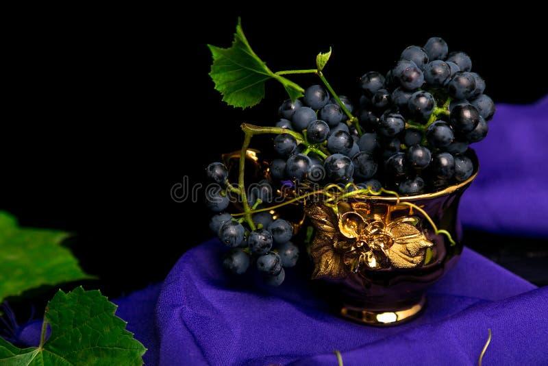 Σταφύλια κόκκινου κρασιού στο χρυσό φλυτζάνι στο ιώδες υπόβαθρο στοκ εικόνες με δικαίωμα ελεύθερης χρήσης