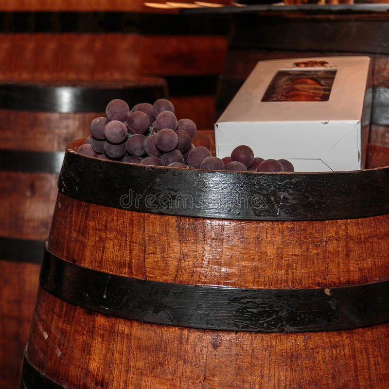 Σταφύλια και κιβώτιο μπουκαλιών στο λεπτό μεγάλο ξύλινο βαρέλι κρασιού στοκ εικόνα