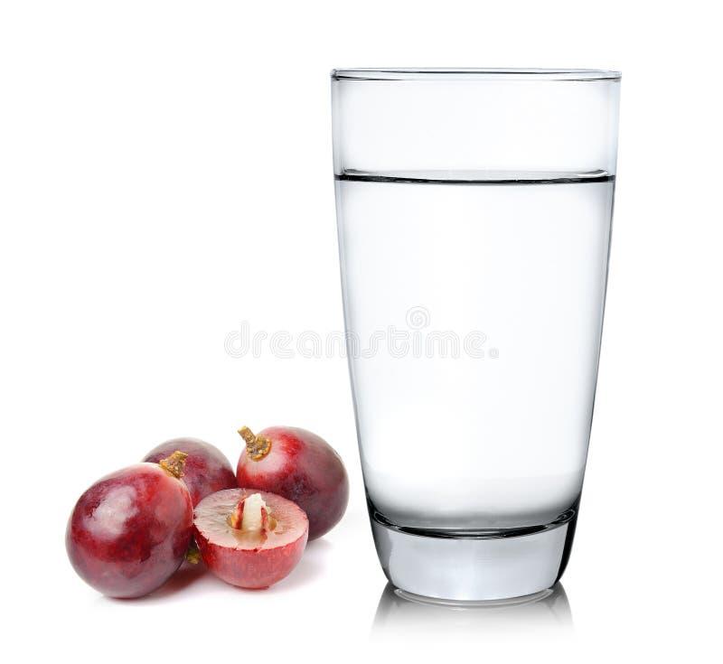 Σταφύλια και ποτήρι του νερού πέρα από το άσπρο υπόβαθρο στοκ εικόνα