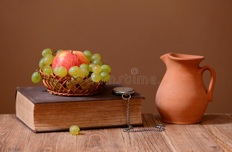 Σταφύλια, μήλα, βιβλία και κεραμική καράφα στοκ φωτογραφία με δικαίωμα ελεύθερης χρήσης