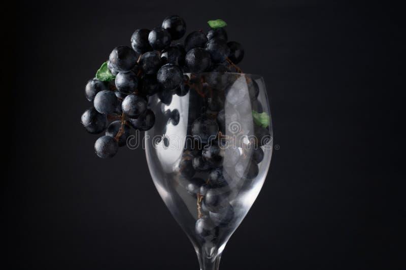 Σταφύλια στην ένωση γυαλιού κόκκινου κρασιού στο σκοτεινό κλίμα στοκ εικόνες
