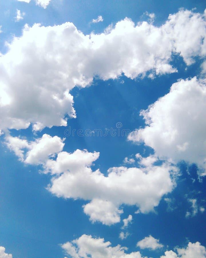 Στα ηλιακά σύννεφα σωρειτών μπλε ουρανού άσπρα υπό μορφή καρδιάς στοκ φωτογραφία
