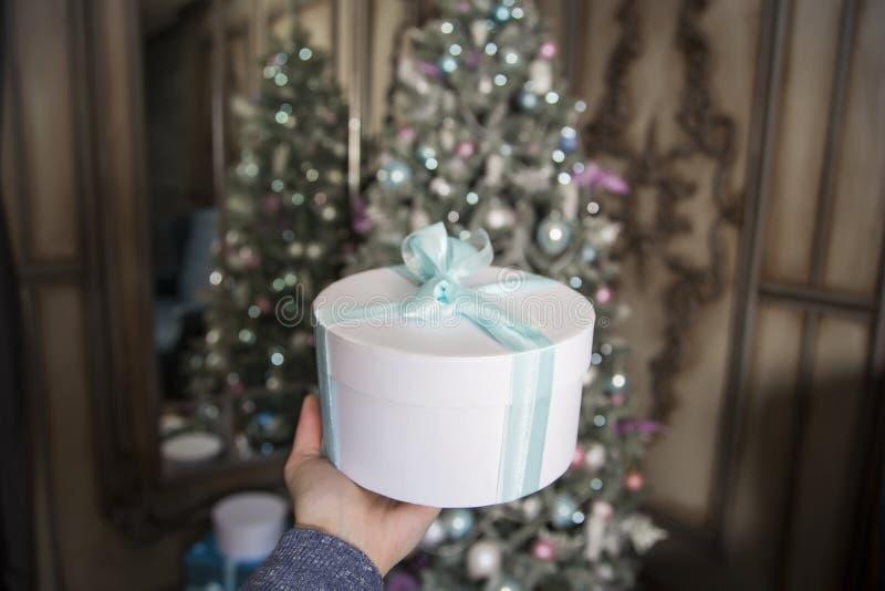Στα πλαίσια διακοσμημένο fir-tree του νέου έτους το θηλυκό χέρι κρατά ένα άσπρο δώρο με μια πράσινη ταινία στοκ φωτογραφίες