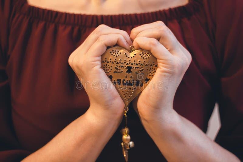 Στα τρυφερά θηλυκά χέρια μια χρυσή καρδιά συμπιέζεται στοκ φωτογραφίες
