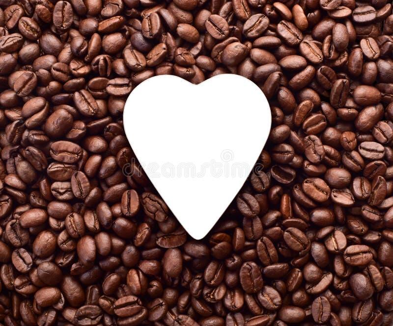 Στα φασόλια καφέ μια άσπρη καρδιά στοκ φωτογραφίες