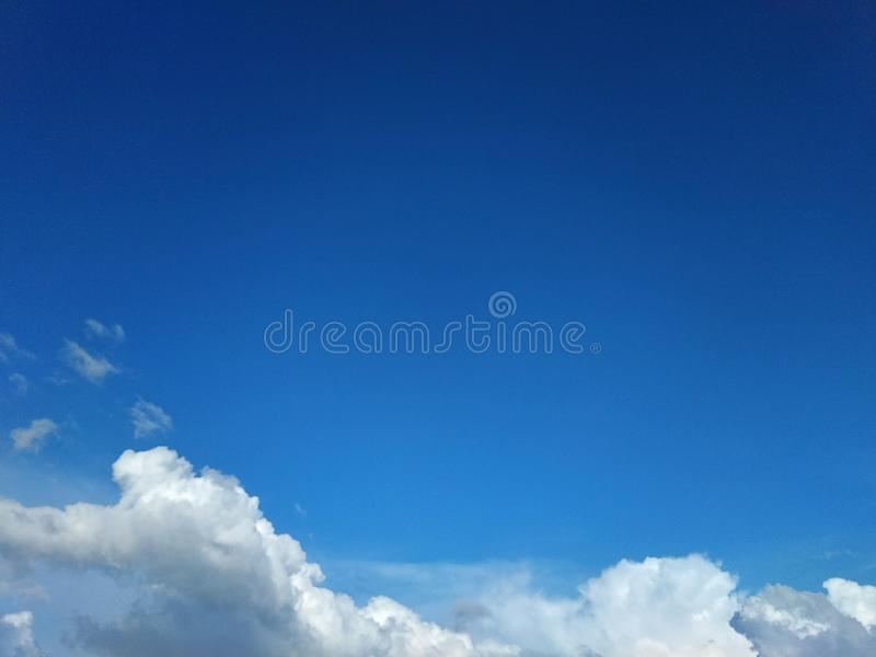 Στα φωτεινά σύννεφα μπλε ουρανού στοκ εικόνα με δικαίωμα ελεύθερης χρήσης