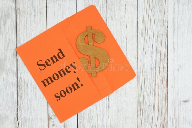 Στείλετε το κείμενο χρημάτων σύντομα με το σύμβολο σημαδιών δολαρίων με τον πορτοκαλή φάκελο στο κατασκευασμένο ξύλινο γραφείο στοκ φωτογραφία