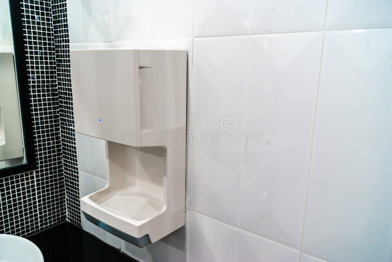 Στεγνωτήρας χεριών στον κεραμικό τοίχο, υγιεινός και την υψηλή τεχνολογία στοκ φωτογραφίες