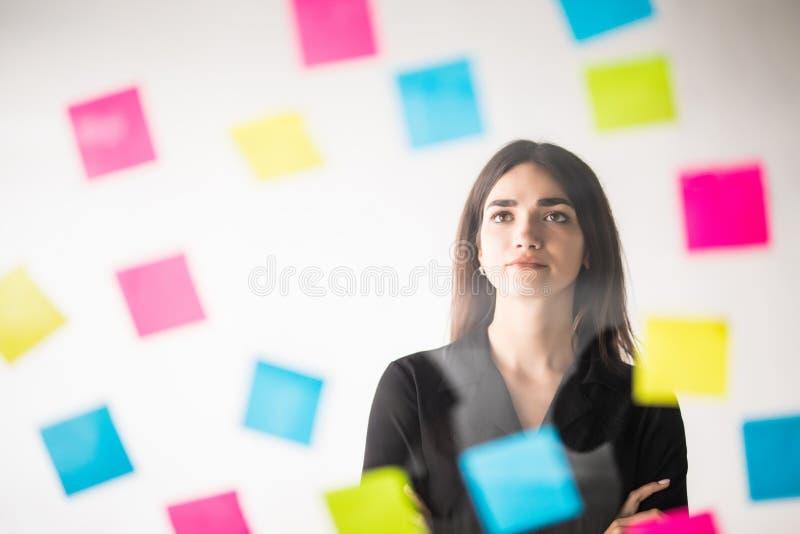 Στεμένος μπροστά από τη νέα επιχειρησιακή γυναίκα τοίχων γυαλιού με μετα αυτό τις αυτοκόλλητες ετικέττες απόφαση γραφείων στοκ εικόνες