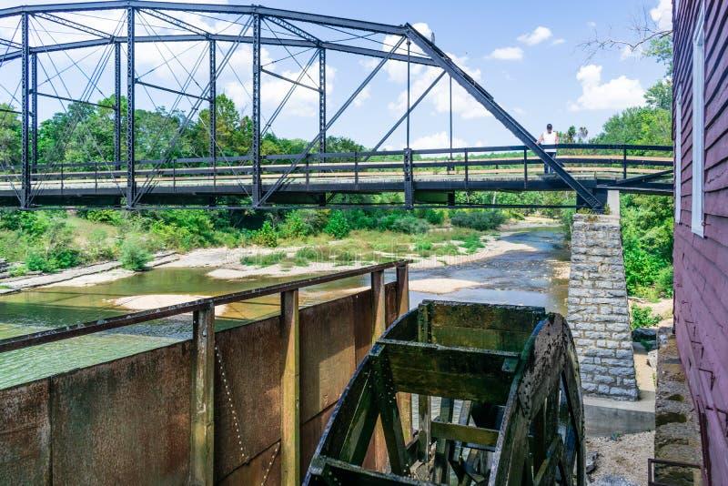 Στεμένος στην ιστορική γέφυρα πολεμικών αετών σε Rogers, το Αρκάνσας ένα μπορεί να δει το λειτουργώντας υδραυλικό τροχό που τροφο στοκ εικόνα