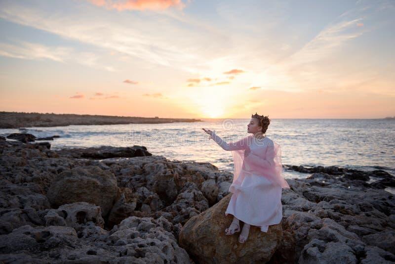στεμμένη η κορίτσι πριγκήπισσα συναντά την αυγή της συνεδρίασης ήλιων σε μια πέτρα στην ωκεάνια ακροθαλασσιά στοκ φωτογραφία με δικαίωμα ελεύθερης χρήσης
