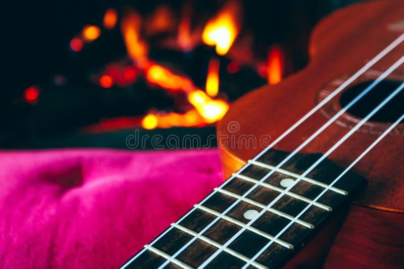 Στενά επάνω τσιμπήματα κιθάρων Ukulele μικρά, εστία στο backgroun στοκ εικόνες