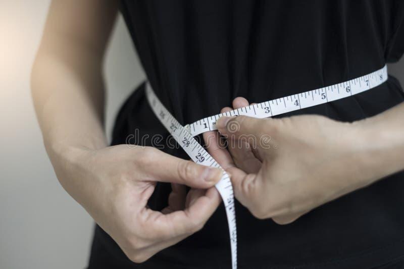 Στενές επάνω γυναίκες έννοιας διατροφής που μετρούν την περιφέρεια μέσης στοκ εικόνες