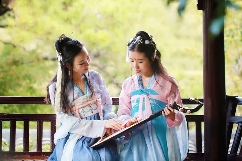 Στενές φίλες bestie στην κινεζική παραδοσιακή αρχαία κιθάρα λαγούτων pipa παιχνιδιού κοστουμιών στοκ εικόνα με δικαίωμα ελεύθερης χρήσης