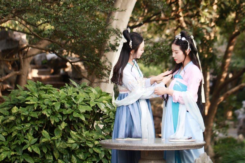 Στενές φίλες bestie στο κινεζικό παραδοσιακό αρχαίο γέλιο συζήτησης συνομιλίας κοστουμιών στοκ εικόνες