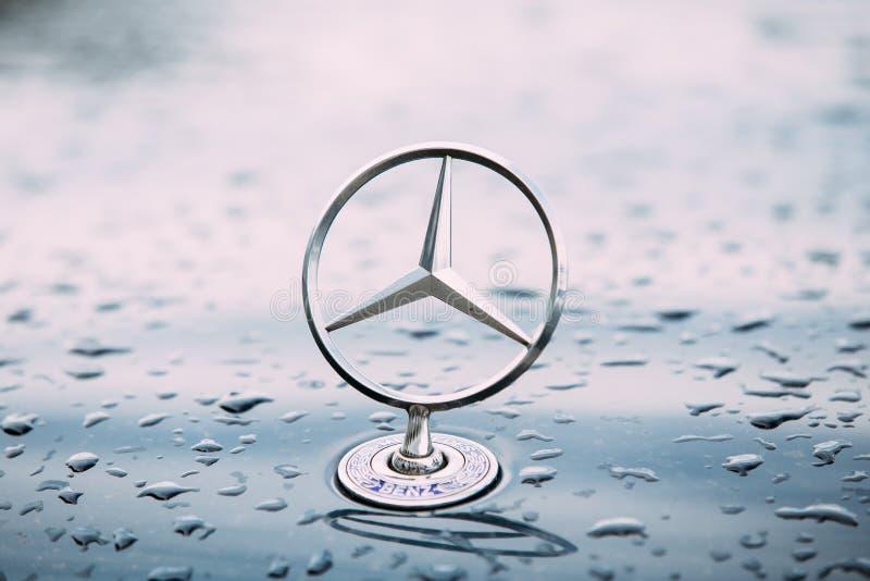 Στενή άποψη του λογότυπου αστεριών μετάλλων Benz της Mercedes στην υγρή κουκούλα του μπλε στοκ εικόνα