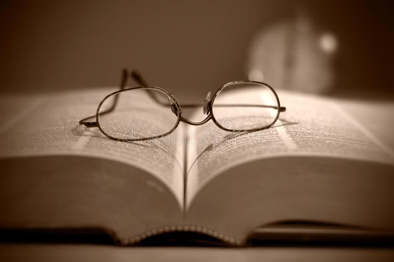 Στενή άποψη Eyeglasses ανάγνωσης στη μεγάλη σέπια βιβλίων που τονίζονται στοκ εικόνες
