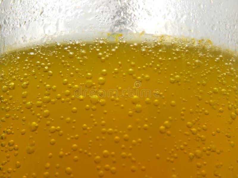 Στενή επάνω, φρέσκια κίτρινη φυσαλίδα υποβάθρου από την πεταγμένη βιταμίνη C στο νερό στο γυαλί στοκ φωτογραφίες