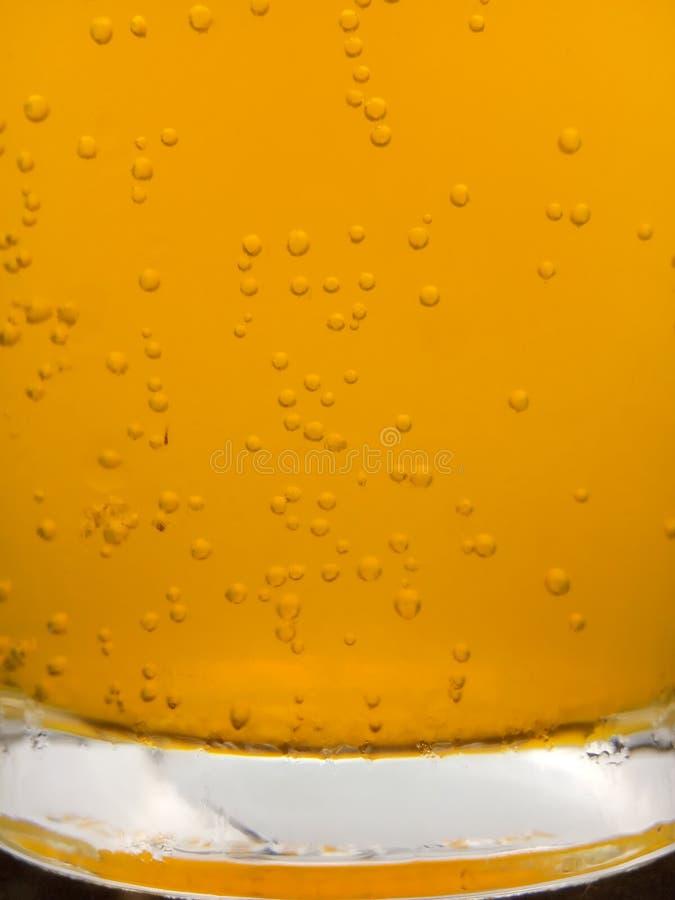 Στενή επάνω, φρέσκια κίτρινη φυσαλίδα υποβάθρου από την πεταγμένη βιταμίνη C στο νερό στο γυαλί στοκ εικόνες