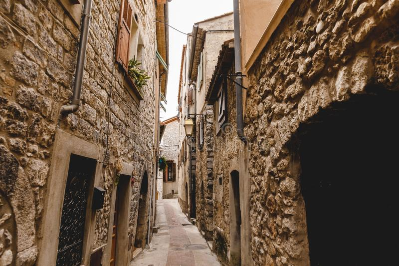 στενή οδός με τα αρχαία κτήρια πετρών στην παλαιά ευρωπαϊκή πόλη, Peille, Γαλλία στοκ εικόνες