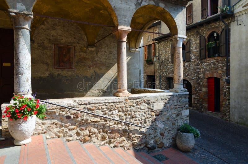 Στενή οδός στην πόλη Sirmione, Ιταλία Εκκλησία της Σάντα Μαρία Maggiore XV αιώνας στοκ εικόνα με δικαίωμα ελεύθερης χρήσης