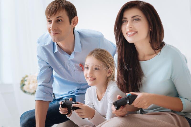 Στενή οικογένεια της Νίκαιας που παίζει τα τηλεοπτικά παιχνίδια στοκ φωτογραφία με δικαίωμα ελεύθερης χρήσης