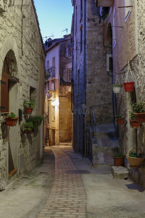 Στενή οδός με τα λουλούδια στην παλαιά πόλη Peille στη Γαλλία Nig στοκ φωτογραφίες