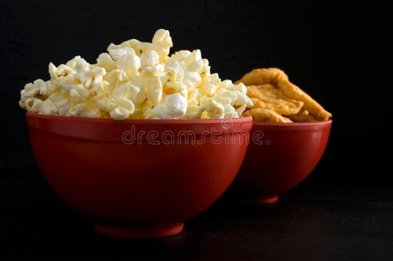 Στενή πλάγια όψη των βουτυρωμένων Popcorn και BBQ τσιπ ρυζιού στα κόκκινα κύπελλα που απομονώνονται στο Μαύρο στοκ εικόνα