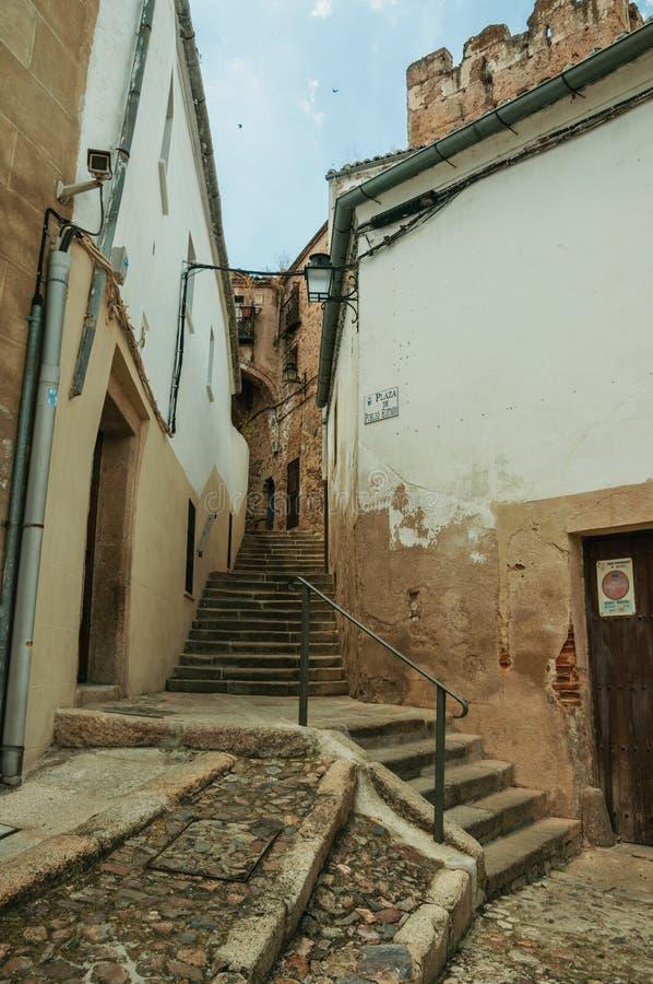 Στενωπός με τη σκάλα στην κλίση στη μέση των παλαιών κτηρίων σε Caceres στοκ εικόνα