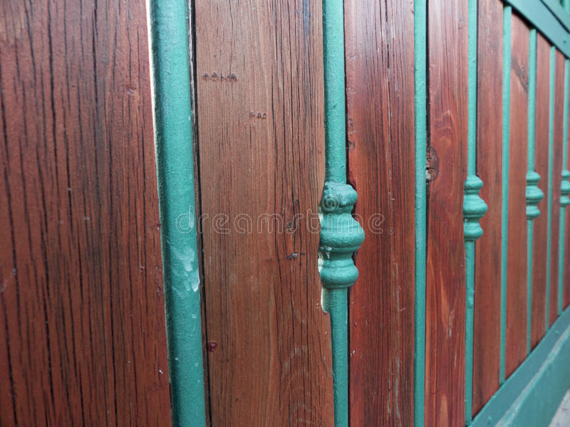 Στενός ένας επάνω μιας σύγχρονης πύλης χάλυβα που καλύπτεται από μερικές ξύλινες επιτροπές στοκ φωτογραφία